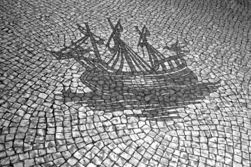 Fotografia de uma calçada típica Portuguesa com uma caravela portuguesa